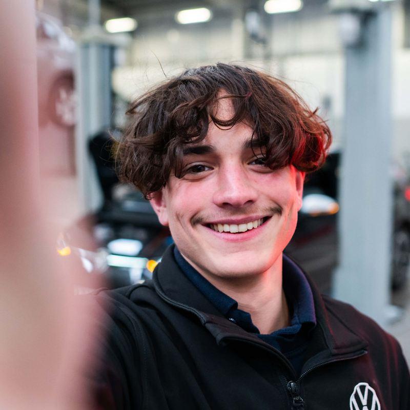 A selfie of a VW technician in a workshop