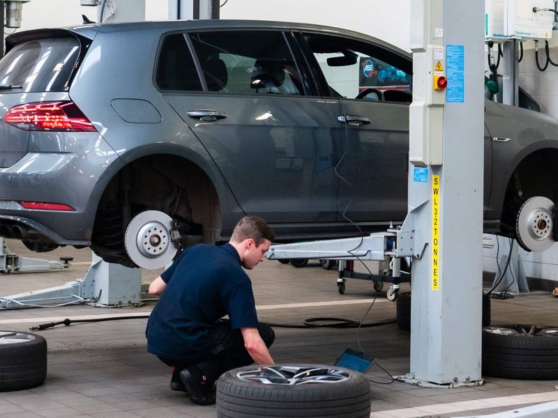 A VW technician knelt next to an exposed brake disc and pad
