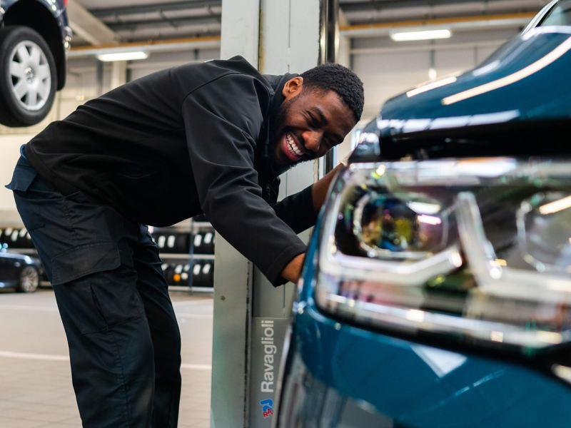 VW technician bent down next to a blue Tiguan next to the headlight