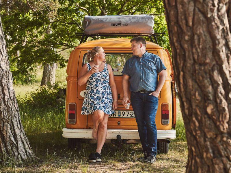 Man och kvinna står vid sin gula VW folkabuss campingbil