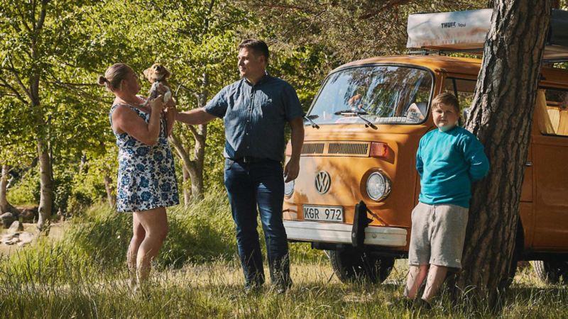 Familj framför en gul VW folkabuss campingbil