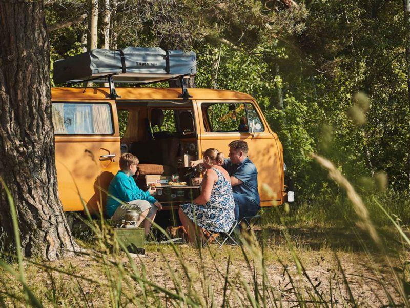 Familj fikar framför gul VW folkabuss campingbil