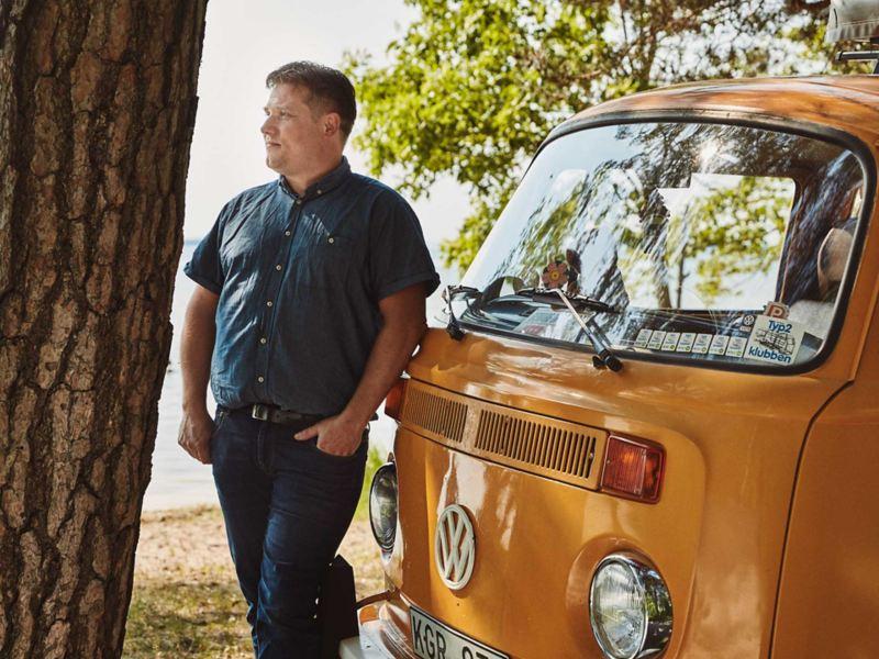 Man står vid sin gula VW folkabuss campingbil