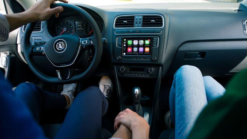 Pareja en cabina de Volkswagen tomados de la mano. El plan perfecto para celebrar San Valentín