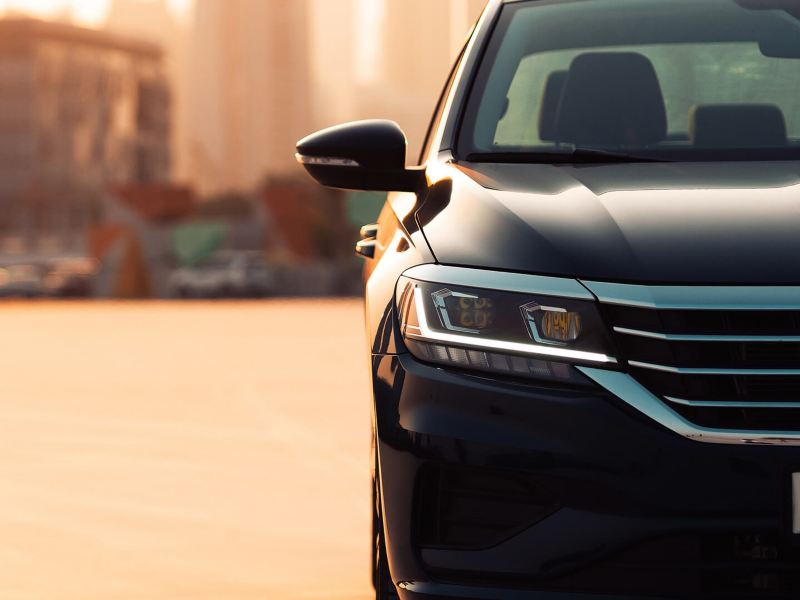 The 2020 Volkswagen Passat front view, half of the car is shown, with the headlights on