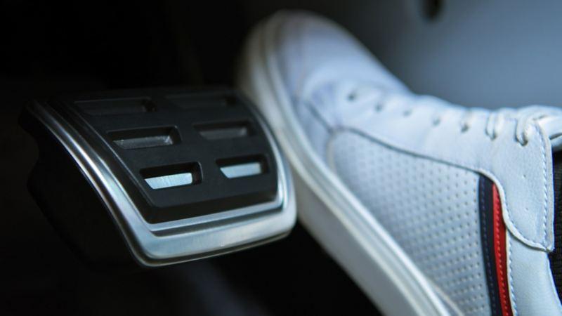 Pie sobre pedal de auto Volkswagen siguiendo los consejos para manejar bajo lluvia