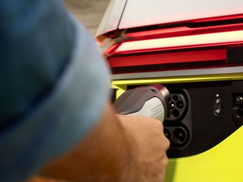"""Un uomo mette in carica, presso una Wallbox, un ID. Buzz Volkswagen, con dettaglio sulla """"spina Mennekes""""."""