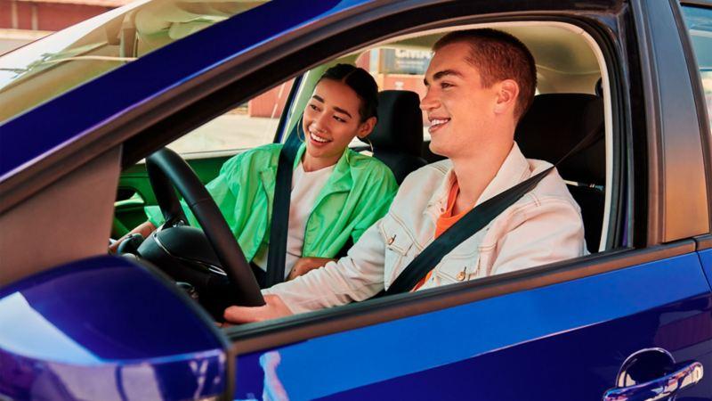 Pareja alegre al interior de Polo 2020 de Volkswagen equipado con los mejores sistemas de seguridad