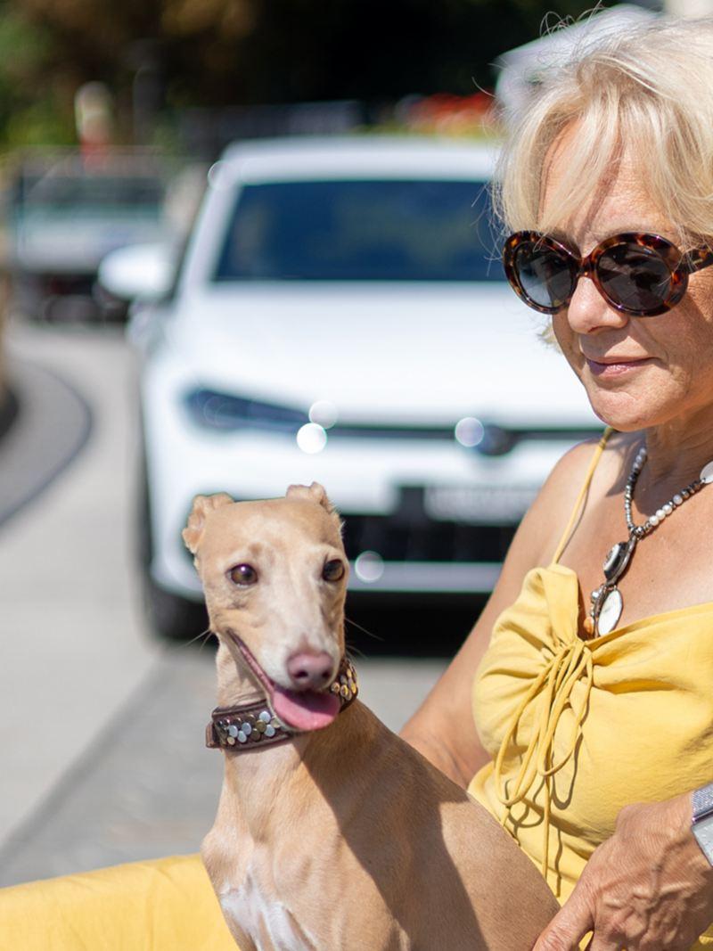 Marilena Bachmann est assise sur un banc avec son chien Limbo et la nouvelle Polo est garée derrière eux.