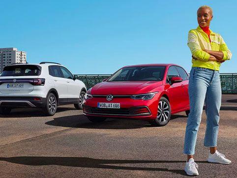 Une femme se tient devant une voiture