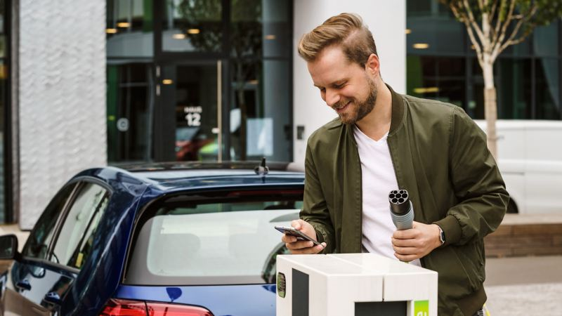 A man using his mobile app to make a payment at a charging station