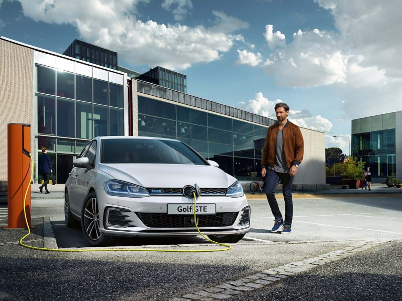 A man walking past a Golf GTE being charged in an office car park