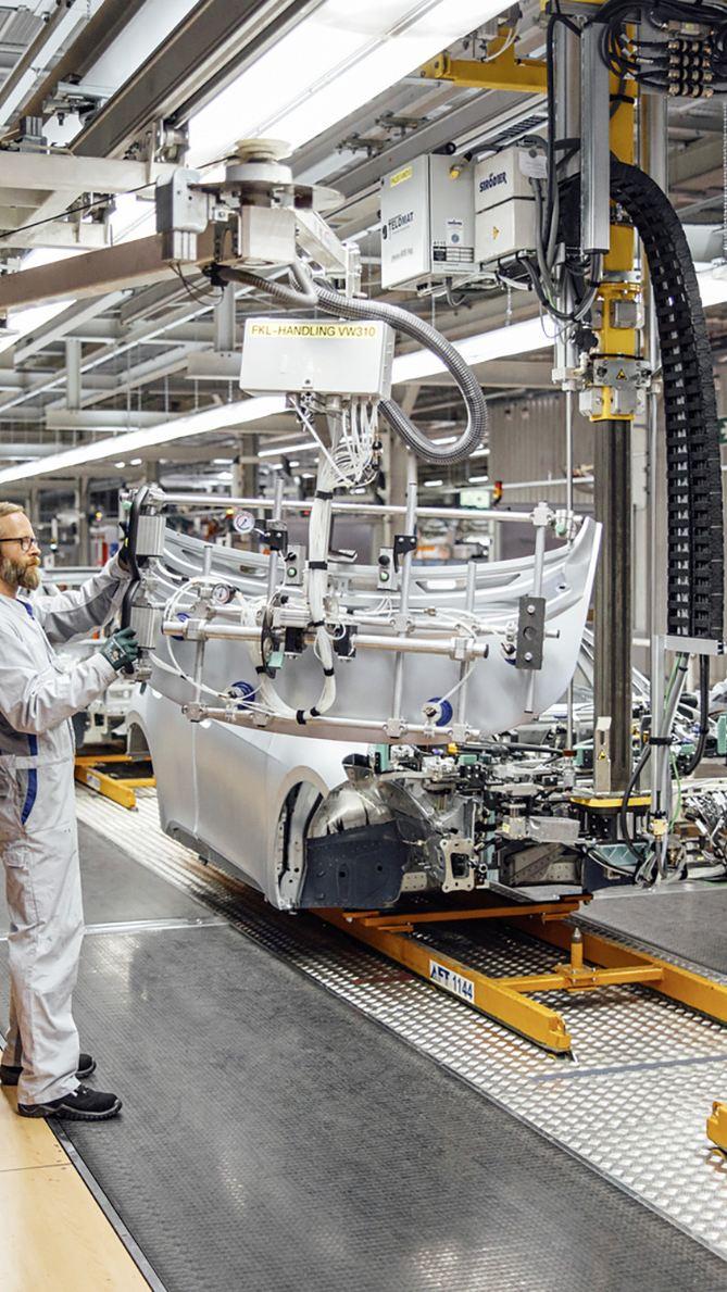 Rohkarossen fahren über eine Montagelinie in einem Automobilwerk.