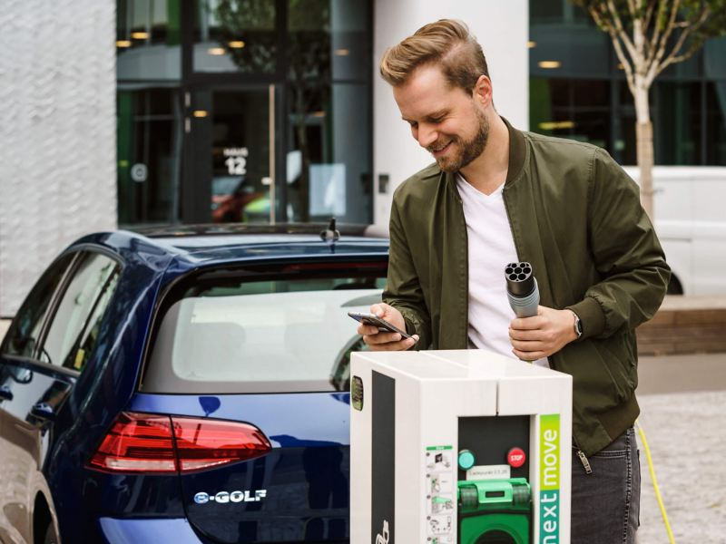 A man standing behind an e-Golf and using his mobile app with the charging station