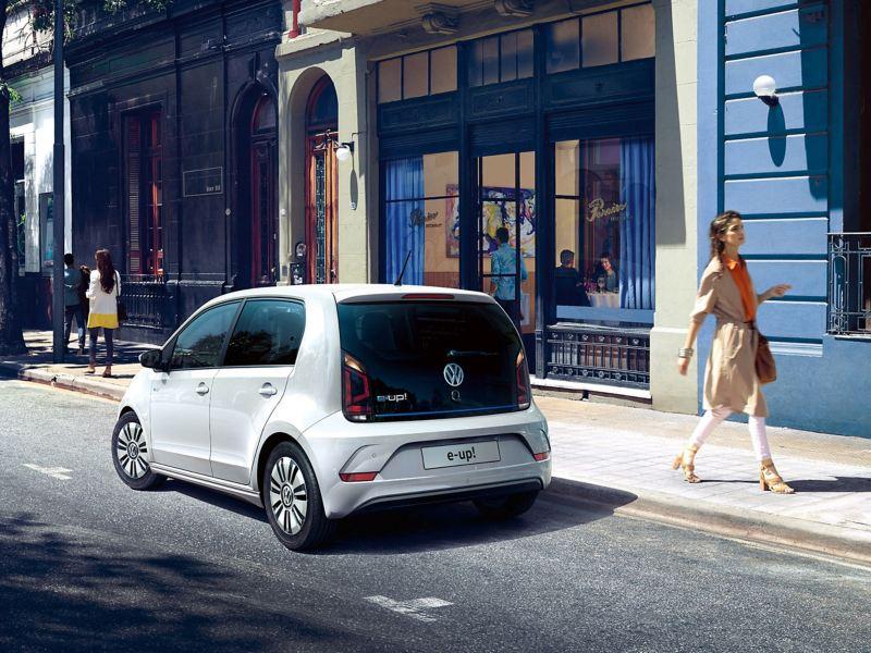 A white Volkswagen e-up! in a cobbled shopping street, pedestrians shopping.