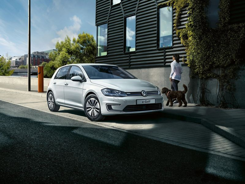 An e-Golf parked on a road and a woman walking a dog on the pavement next to the car