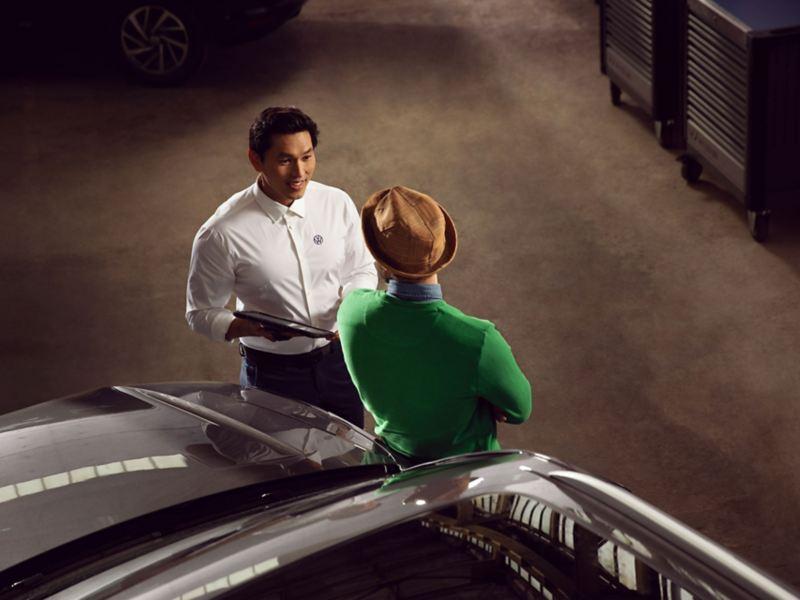 Un collaborateur du service Volkswagen prend en charge le véhicule et parle avec le client