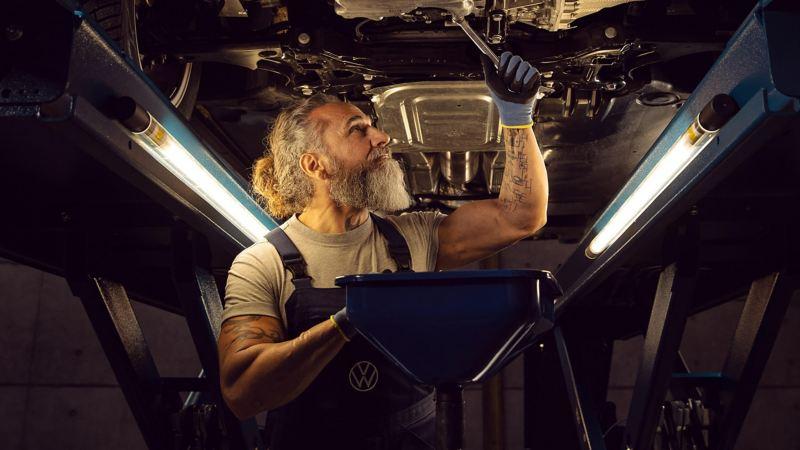 Mechanic inspecting car on ramp