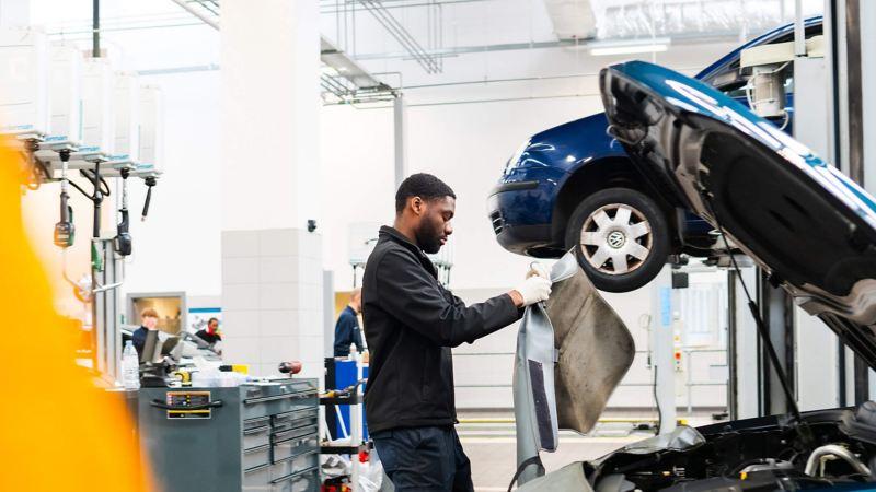 A technician standing over an open bonnet of a VW holding a car cover