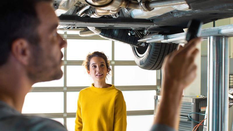 male mechanic servicing vehicle for woman
