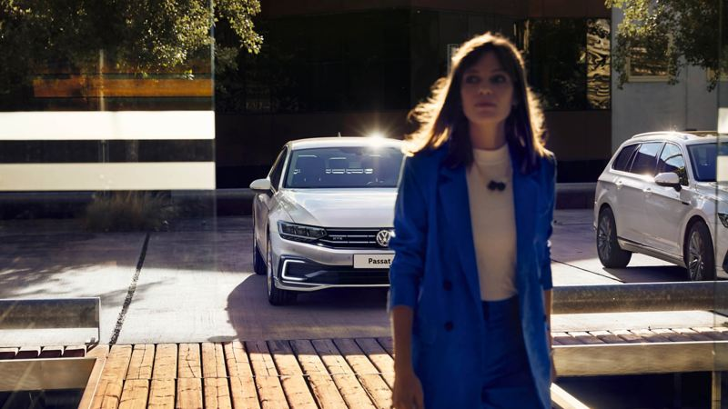 A woman in front of Passat GTE car