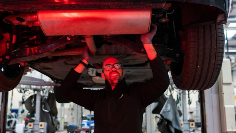 A VW technician inspecting under the chassis of a car