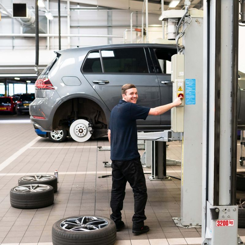 A technician working on a VW golf that's raised on a ramp with the wheel removed