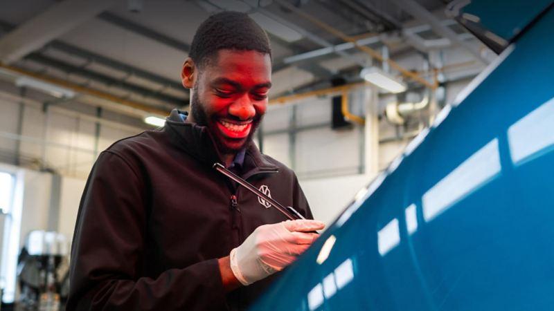 A technician inspecting a window wiper blade on a blue VW car