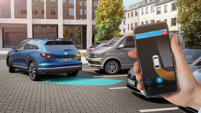Illustration of the Park Assist Plus app being used on a smartphone to park a Touareg