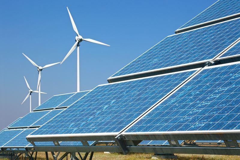 Solaranlage mit Windrädern im Hintergrund.