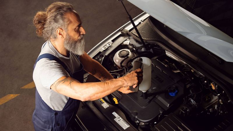 A Volkswagen technician pouring oil into a car engine