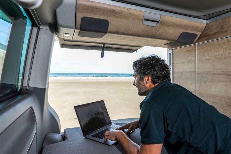 Mężczyzna z laptopem we wnętrzu pojazdu