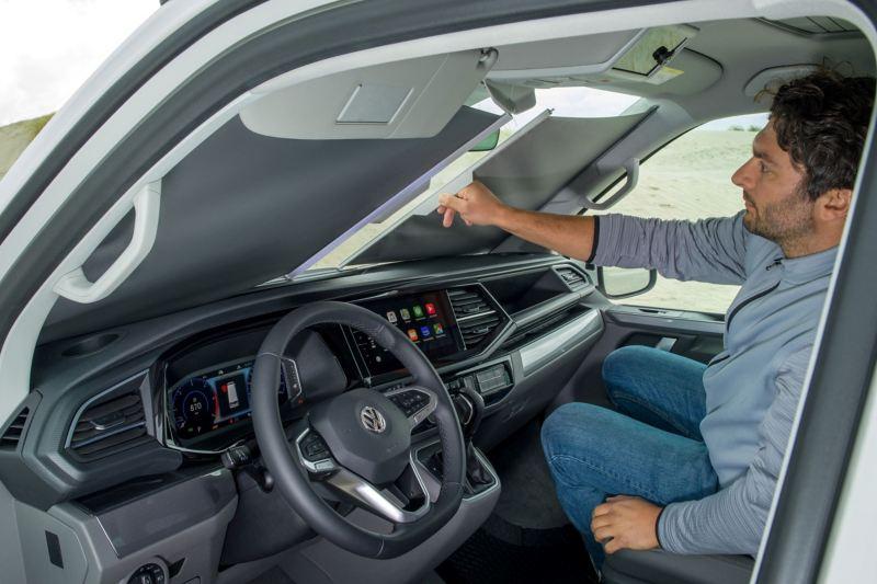 Mężczyzna zasłaniający przednią szybę wewnątrz pojazdu