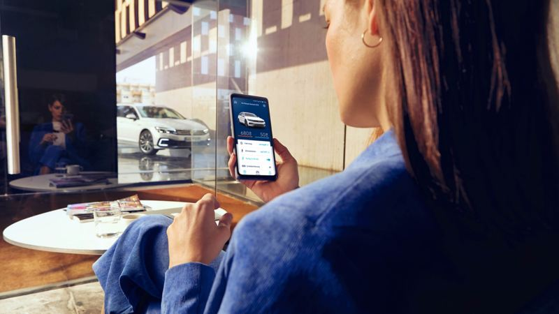 Woman looking at an app on her phone with a Passat GTE parked outside
