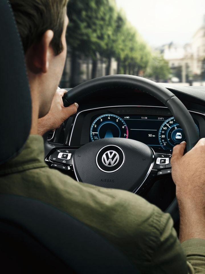 A man is getting in VW car on a driver's seat, link out to VW test drive page