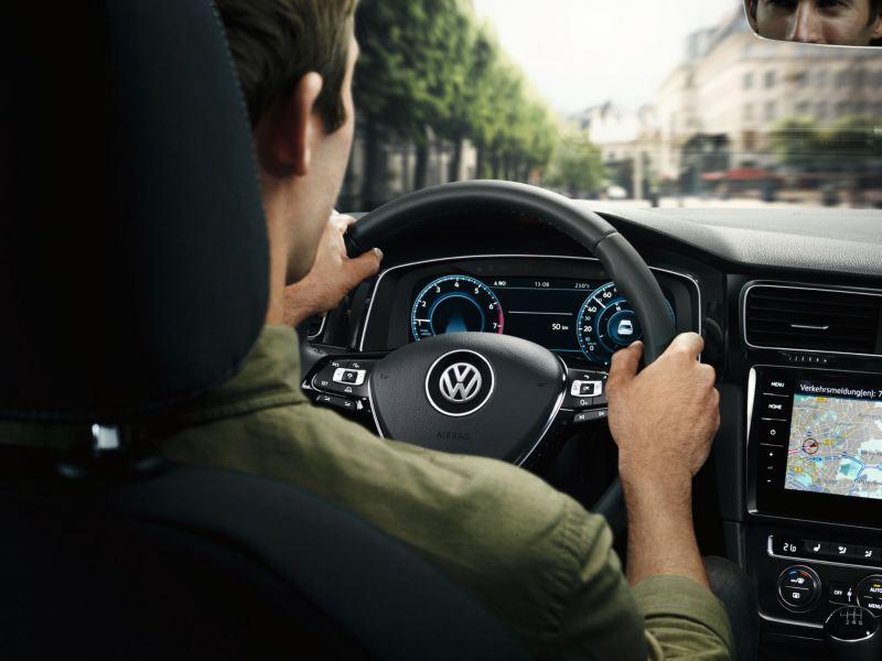 Un homme monte dans une voiture VW sur le siège du conducteur, lien vers la page des essais de conduite VW