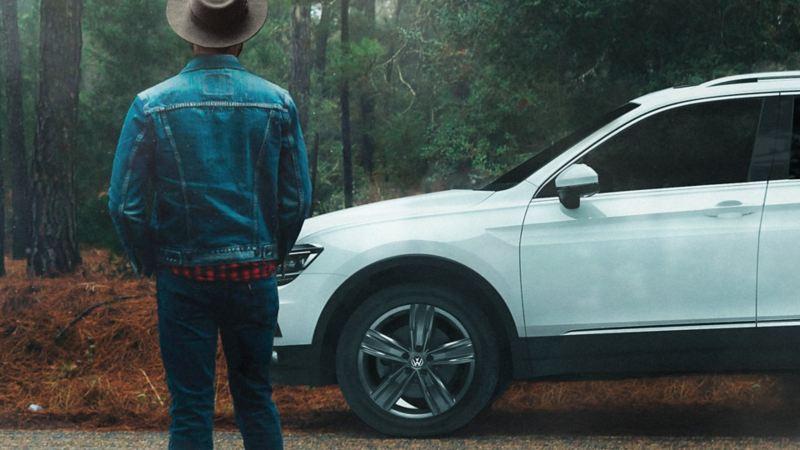 Tiguan 2020, el SUV seguro con mejor desempeño estacionado sobre carretera frente a hombre parado