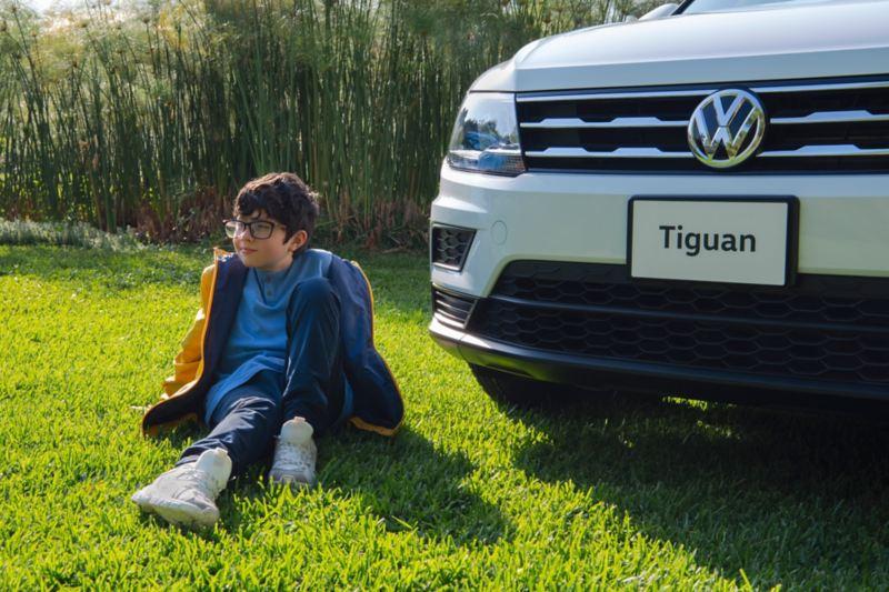 Niño sentado frente a Tiguan 2020,  camioneta familiar VW destacada por su seguridad y potencia