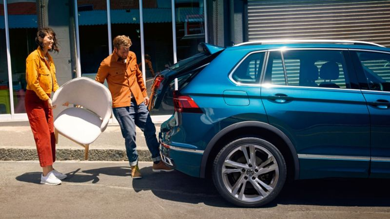 A couple opening the tailgate of the VW Tiguan