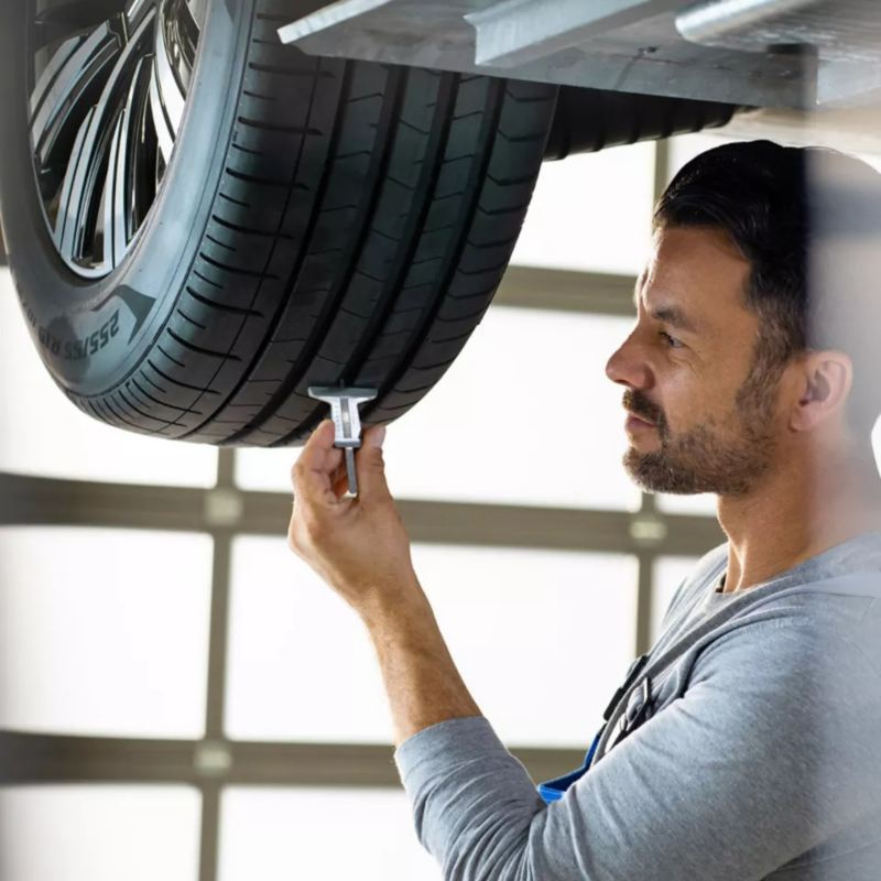 """A person is checking a tire, link out to Vw """"tires"""" page"""