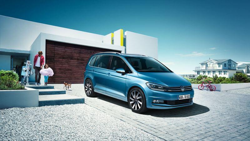 Vooraanzicht VW Touran in een parkeerplaats voor een huis.