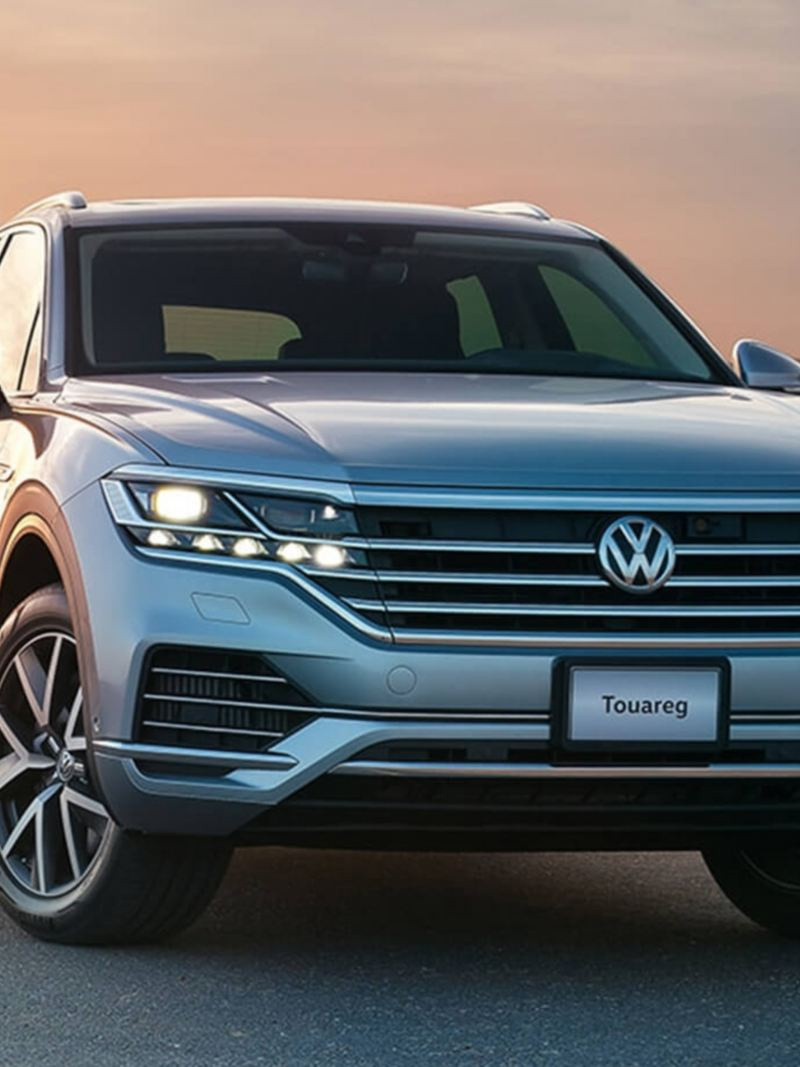 A Volkswagen Touareg parked in the desert with the sun setting behind it