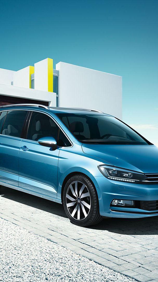 VW Touran parkerad framför en garageport, familj i bakgrunden
