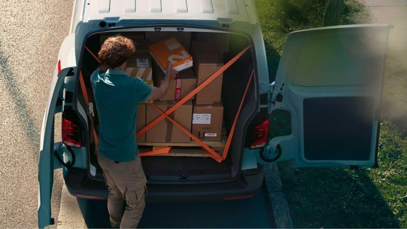 Ein Paketzusteller belädt seinen VW Transporter.