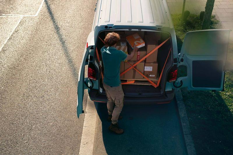 Ein Kurier belädt seinen Transporter mit Paketen.