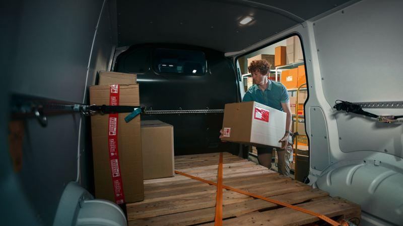 Pakete werden in dem geräumigen Laderaum des VW Transporter verstaut.