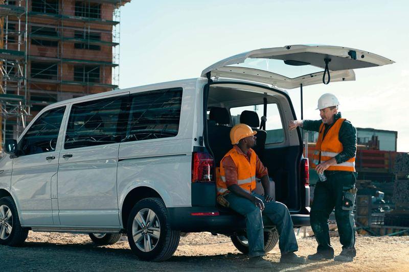 Deux ouvriers du bâtiment font une pause avec le coffre d'un Transporter Volkswagen ouvert.
