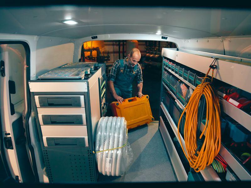 Ein Handwerker verstaut sein Werkzeug in einem umgebauten VW Crafter.
