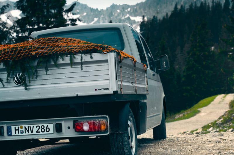 Un VW Transporter plateau 6.1 sur un chemin de terre.