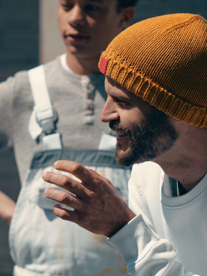 Ein Mann mit orangener Mütze stütz sich auf sein Knie und redet.